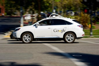 A driver drives a Google Inc. self-driving car in front of the company's headquarters in Mountain View, California on September 27, 2013.