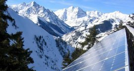 Photo of a solar electric system in Colorado with snow-covered mountain peaks in the background.
